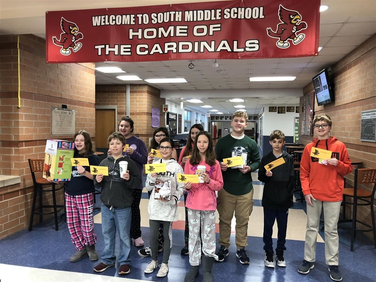 Students pose in the South Middle School entry way with their BINGO prizes. Prizes included star bucks gift cards, a star wars R2D2 lunch box, a pop corn maker and movie tickets!