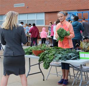 One Thomas students sells some greens to D25 Superintendent Dr. Bein.