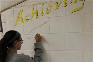 Students signed the C.A.R.D.S. wall representing the CARDS traits.