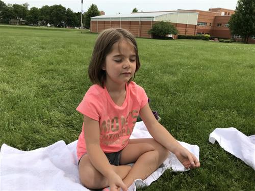 One student sits on the grass with her class as they all close their eyes in a meditation practice.