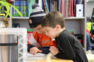 One fifth grader helps a kindergartener with a book.