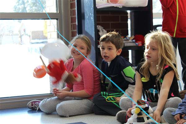 Students watch and hope their elf stays in zip-line car they engineered.